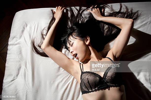 woman in lingerie laying on bed - orgasmo fotografías e imágenes de stock