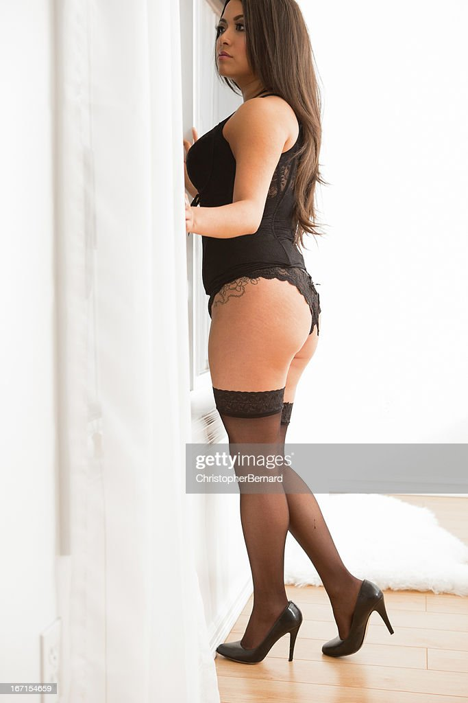 Woman in lingerie looking out window : Stock Photo