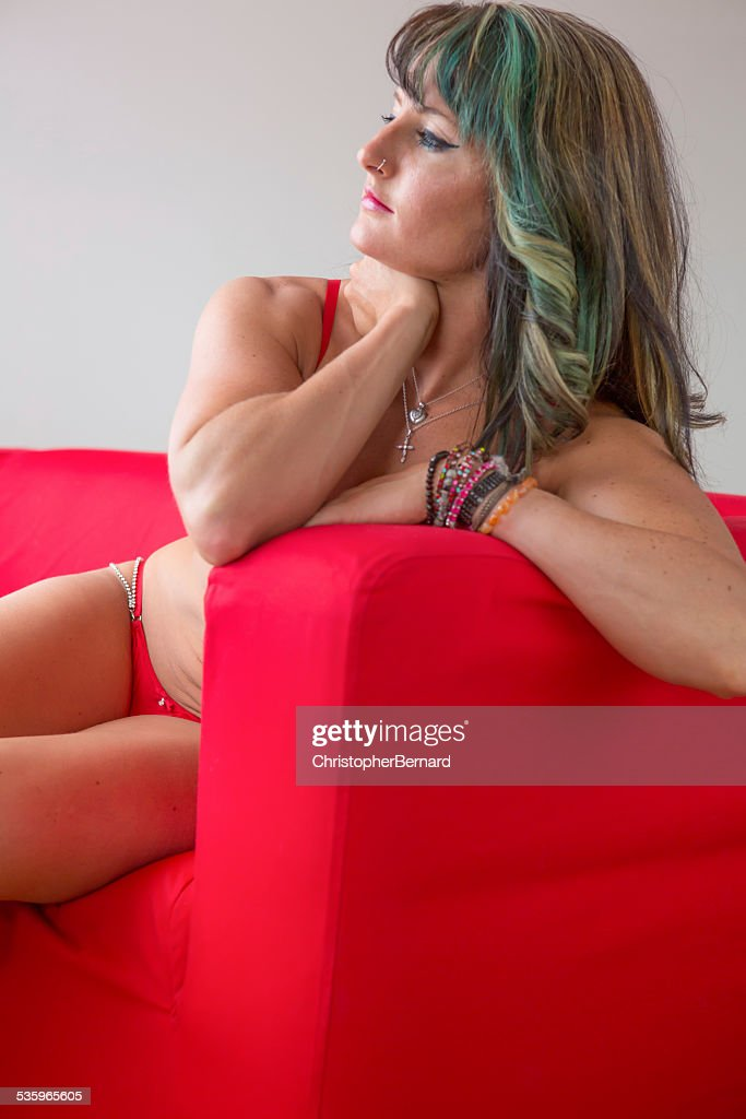 Woman in lingerie on couch. : Stock Photo