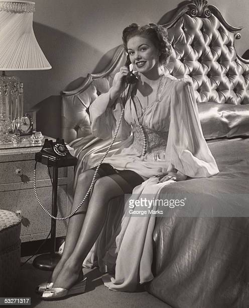 woman in lingerie on phone in bedroom - women wearing garter belts stock photos and pictures