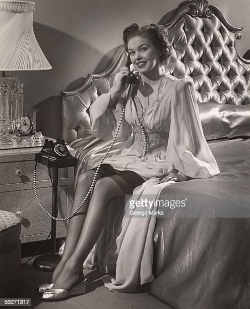 Woman in lingerie on phone in bedroom
