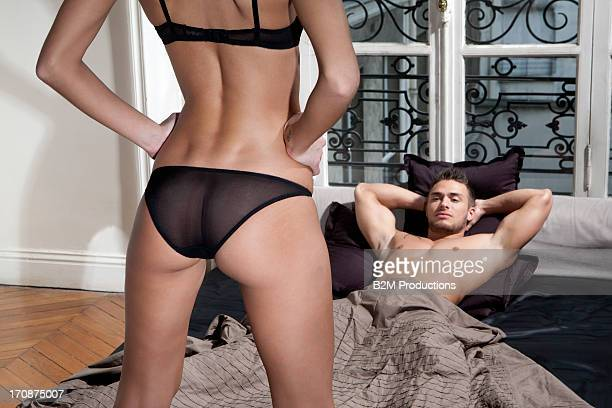 Woman in lingerie standing in front of man