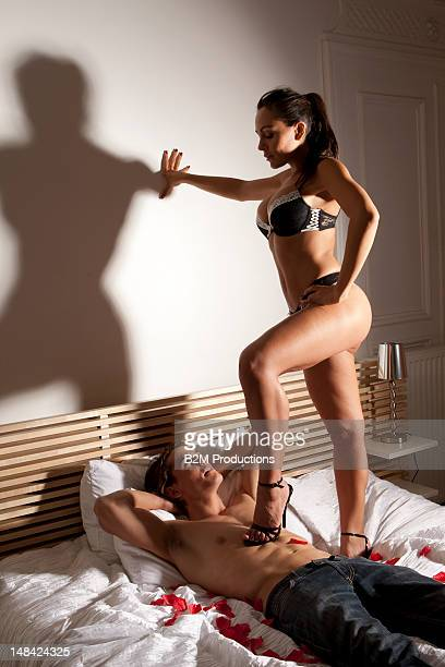 woman in lingerie with her foot on a man's chest - dominatrice photos et images de collection