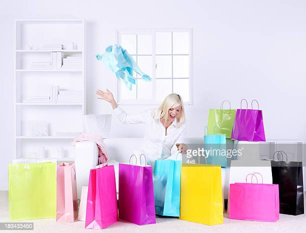 Woman in living room opening presents surrounded by gift bags