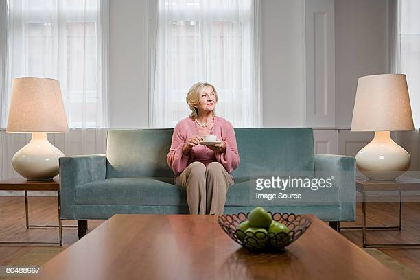 woman in living room - seniore vrouwen stockfoto's en -beelden