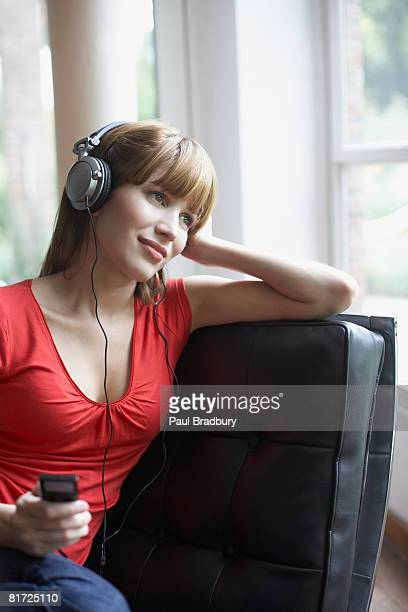 Woman in living room using MP3 player and smiling