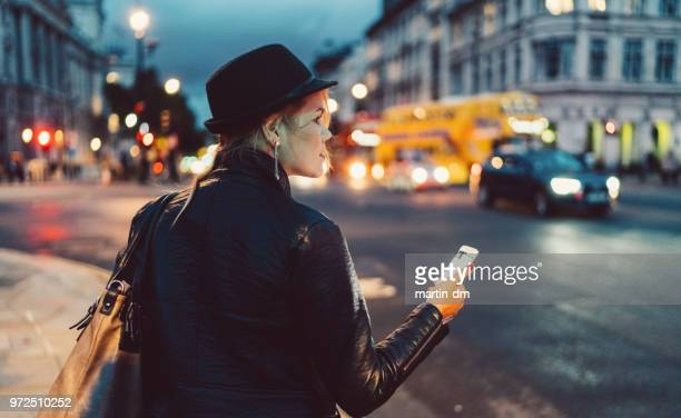 woman in london at night waiting for a taxi - mobile app stock pictures, royalty-free photos & images