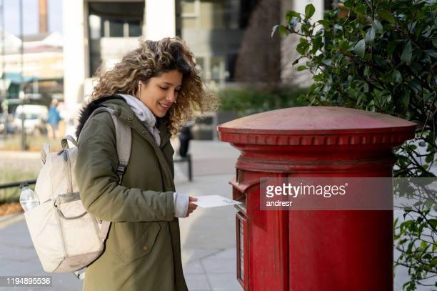 woman in london posting a letter - sending stock pictures, royalty-free photos & images