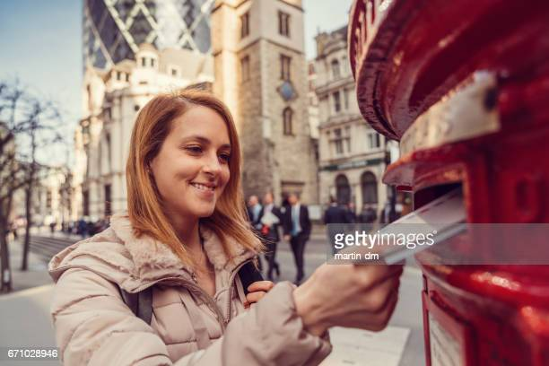 woman in london posting letters in the mailbox - sending stock pictures, royalty-free photos & images