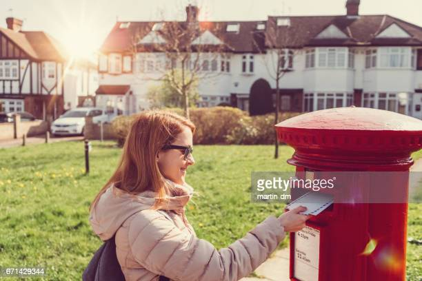 woman in london posting letters in the mailbox - send stock pictures, royalty-free photos & images