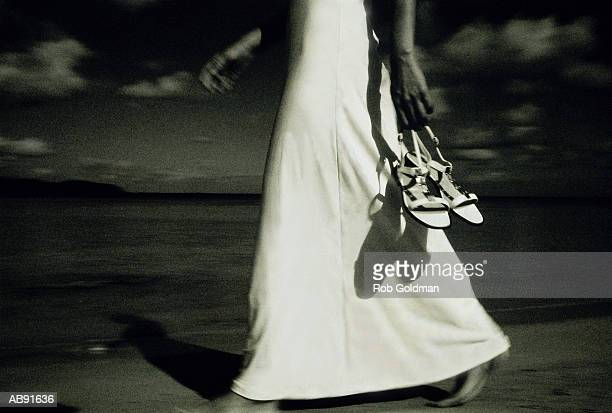 Woman in long dress, carrying shoes on beach, low section (B&W)