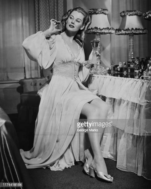 woman in long dress sits at dressing table with parfume - archival stock pictures, royalty-free photos & images