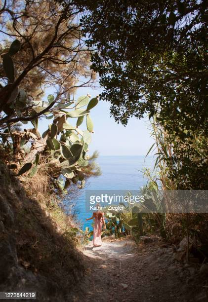 woman in long silky dress walking down a path towards the sea - satin dress stock pictures, royalty-free photos & images