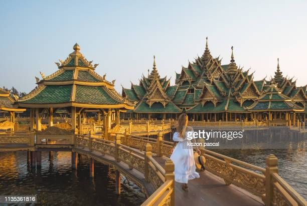 woman in long white dress walking on a bridge in a buddhist temple in thailand during sunset . - tempel stock-fotos und bilder