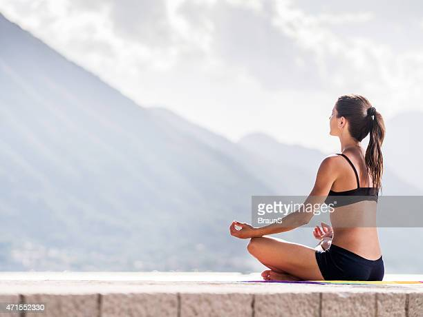 Woman in Lotus position doing breathing exercises at seaside.