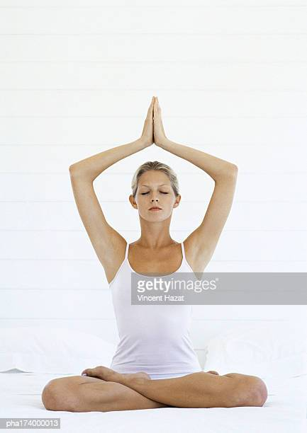 Woman in lotus position, full length, white background