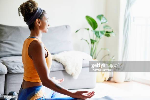 woman in lotus position while working out in living room of home - hair band stock pictures, royalty-free photos & images