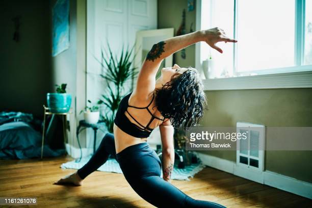 woman in low lunge with backbend pose while practicing yoga in bedroom of home - anstrengung stock-fotos und bilder