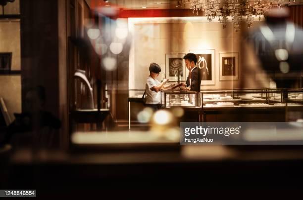 フロント店長の高級ジュエリーブティックビューイングジュエリーの女性 - 宝石店 ストックフォトと画像