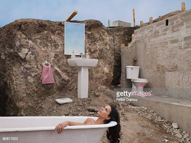 Woman in makeshift bathroom of unfinished house