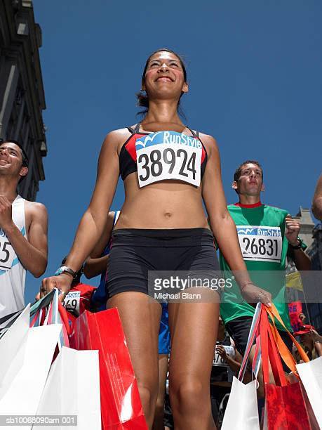 Woman in marathon holding shopping bags