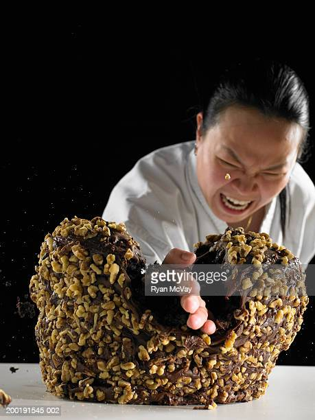 Woman in martial arts outfit performing karate chop on chocolate cake