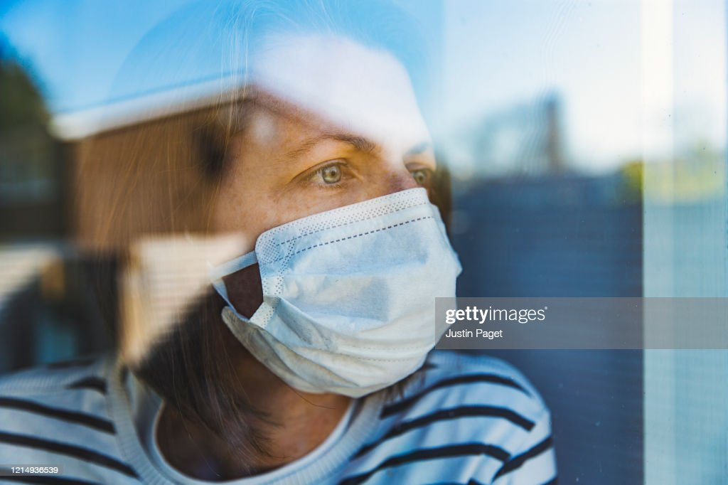 Woman in mask looking through window : Stock Photo