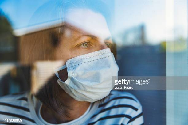 woman in mask looking through window - quarantäne stock-fotos und bilder