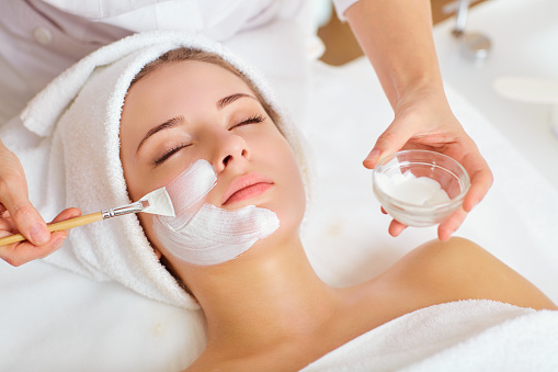 Woman in mask on face in spa beauty salon 921797424