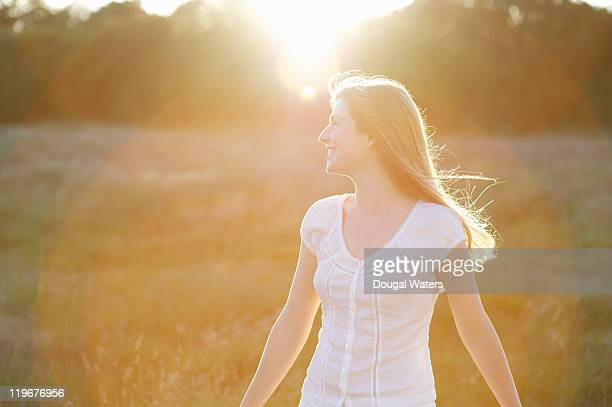 Woman in meadow at sunset.