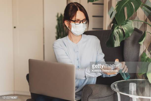 woman in medical protective mask applying an antibacterial antiseptic gel for hands disinfection and health protection during during flu virus outbreak. coronavirus quarantine and novel covid ncov - alcool gel imagens e fotografias de stock