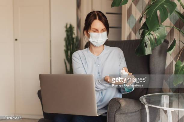 woman in medical protective mask applying an antibacterial antiseptic gel for hands disinfection and health protection during during flu virus outbreak. coronavirus quarantine and novel covid ncov - antiseptic stock pictures, royalty-free photos & images