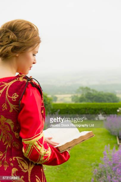 Woman in medieval costume reading book in garden