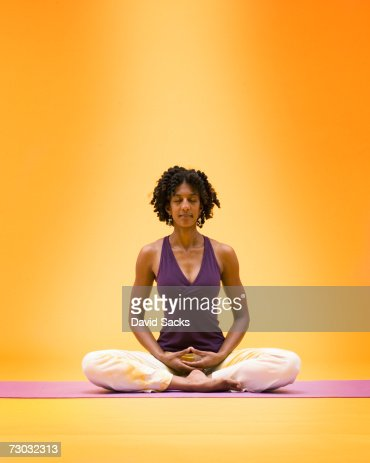 woman in meditation lotus position in yoga studio front