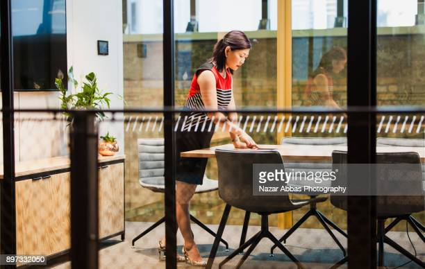 Woman in meeting room preparing presentation.