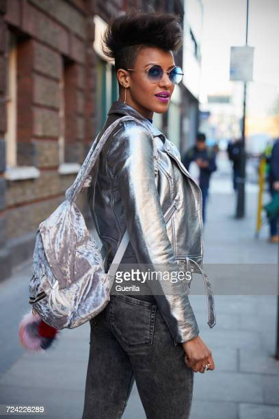 Woman in metallic jacket and backpack standing in a street