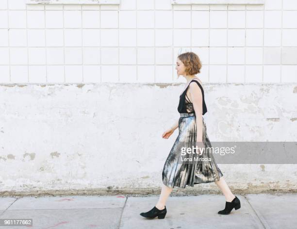 Woman in metallic skirt walking in street, full length, side view