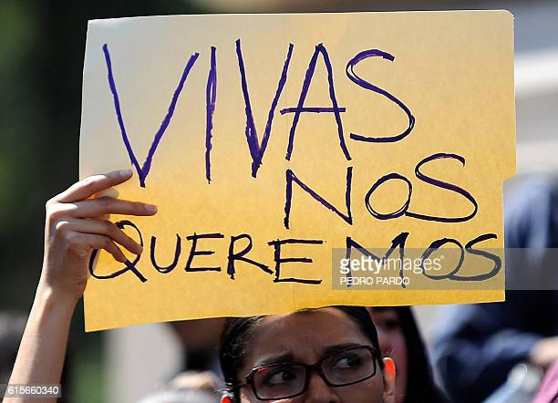 A woman in Mexico City holds a poster reading Vivas Nos Queremos as she takes part on October 19 2016 in a march in solidarity for the brutal killing...