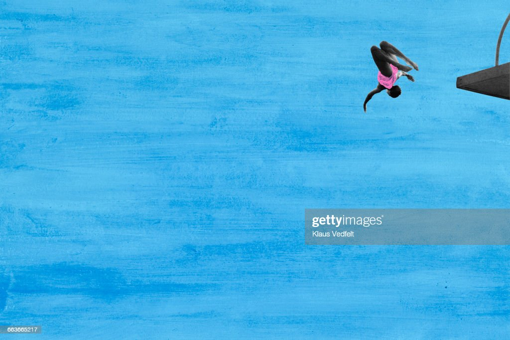 Woman in mid air diving from platform : Stock Photo