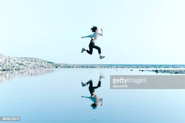 woman in mid-air jump above water reflected in big puddle - puddle stock pictures, royalty-free photos & images