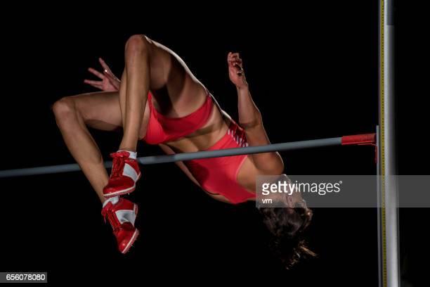 Femme dans les airs en sautant par-dessus une barre horizontale