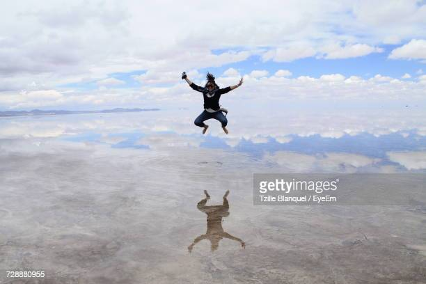 Woman In Mid-Air Jumping Over Salt Lake Against Cloudy Sky At Salar De Uyuni