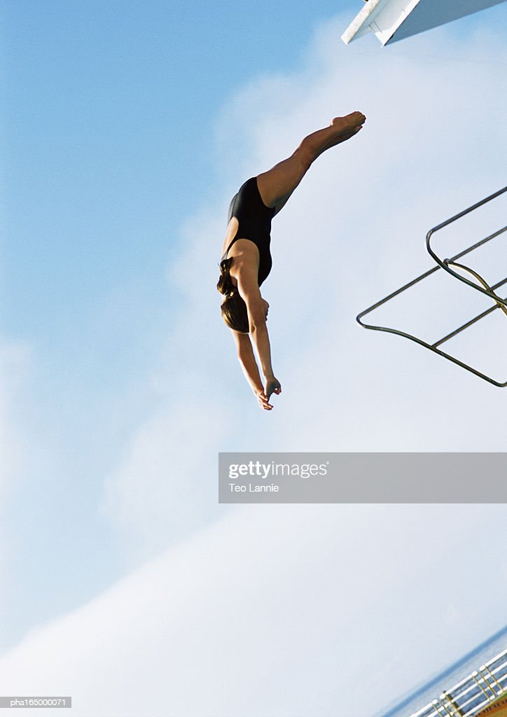 Woman in mid-dive, low angle view, full length, blue sky in background. : Stockfoto