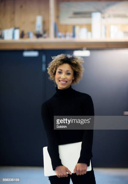 Woman in modern office, holding laptop