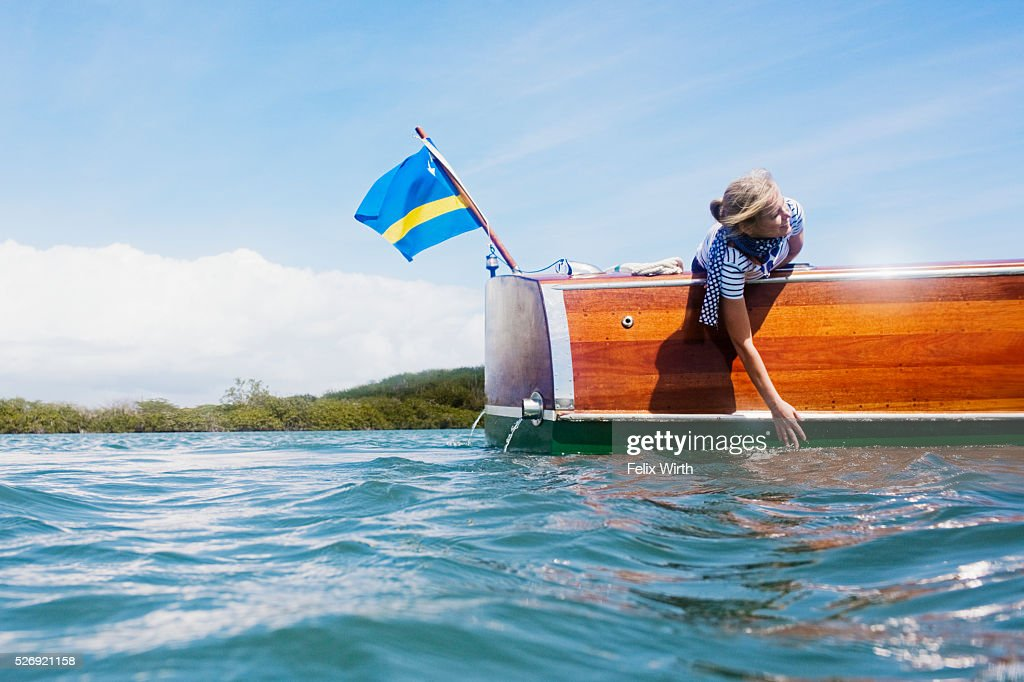 Woman in motorboat playing with waves : Stock-Foto