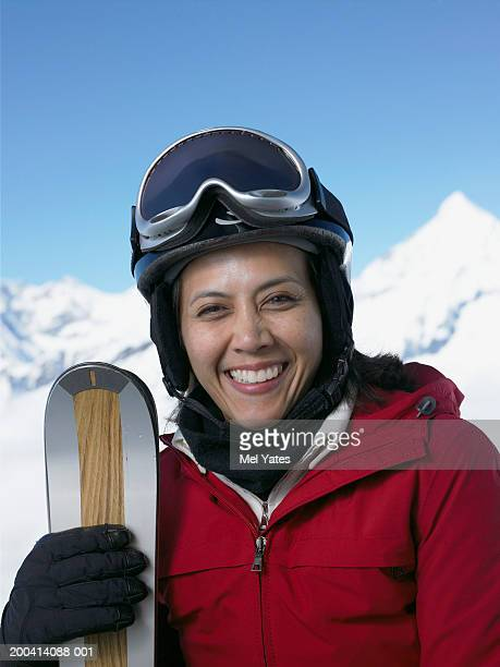 Woman in mountainous snowscape holding skis, smiling, portrait