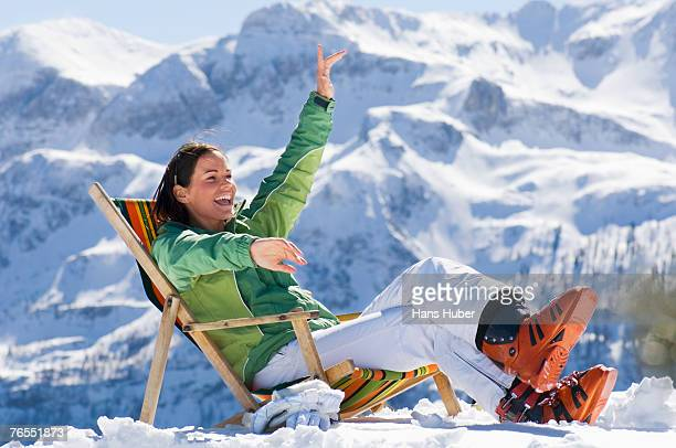 Young woman sitting on deck chair in snow, laughing