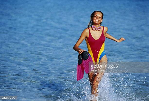 Woman in multicoloured costume running in sea,holding flippers