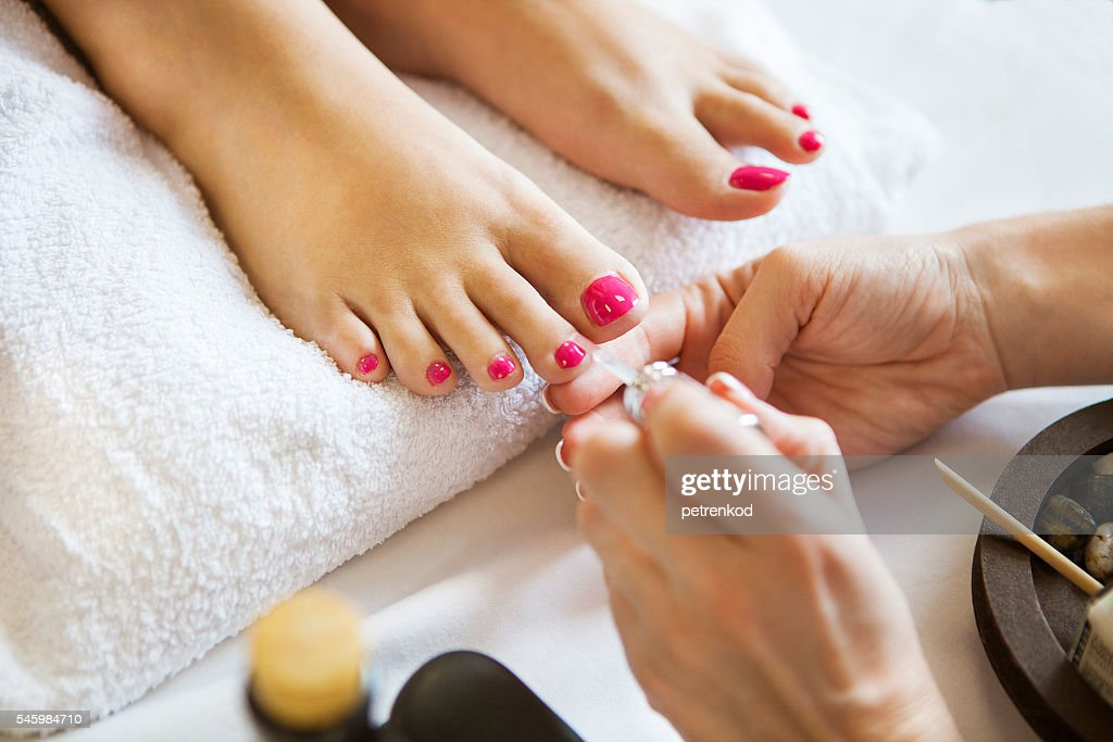 Woman in nail salon receiving pedicure by beautician : Stock Photo