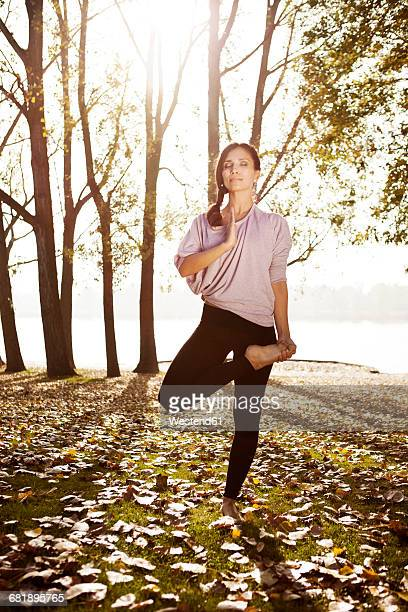 Woman in nature holding a yoga pose